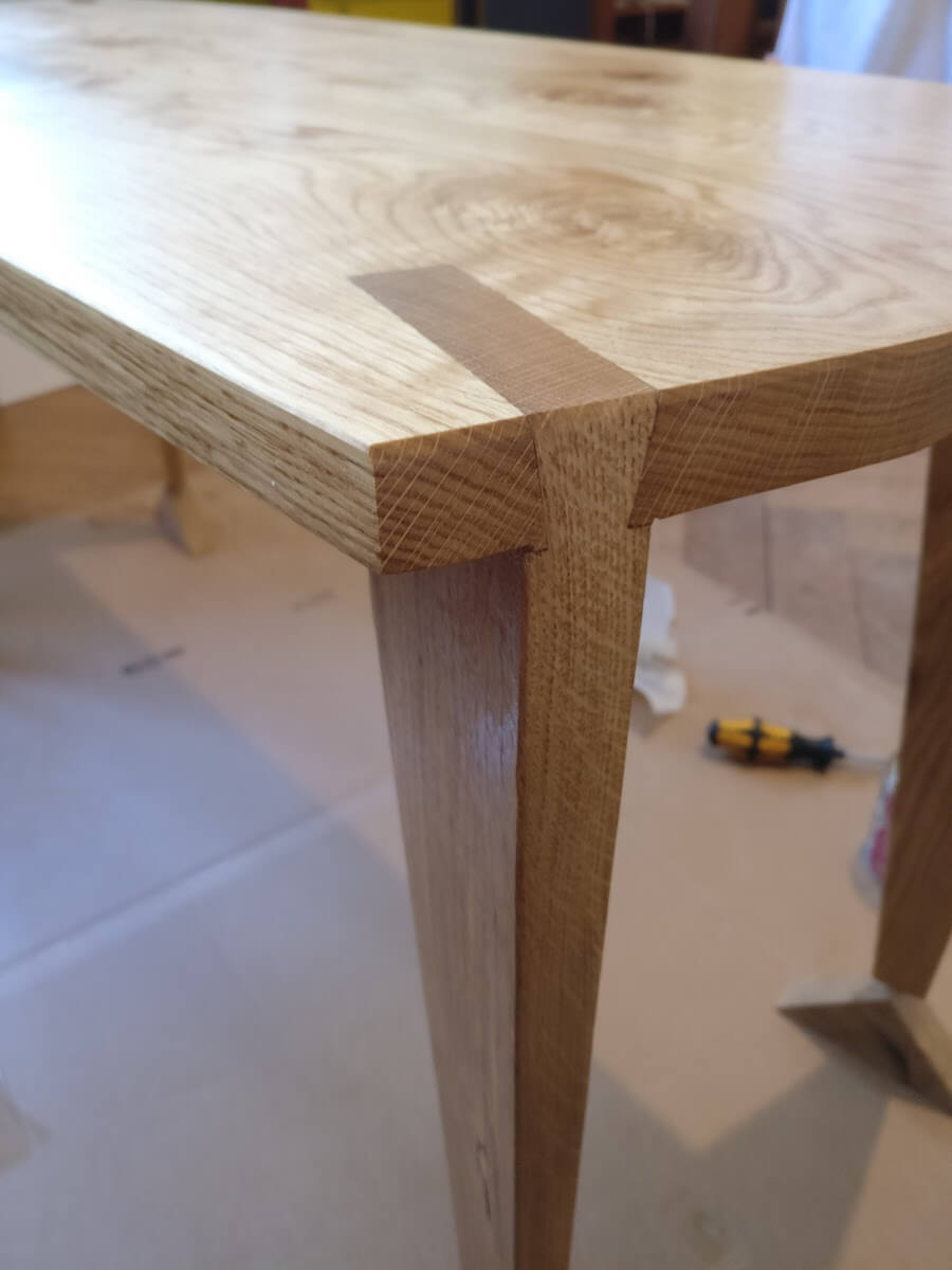 Dovetail with a deeply inset leg that is heavily tapered towards the bottom.